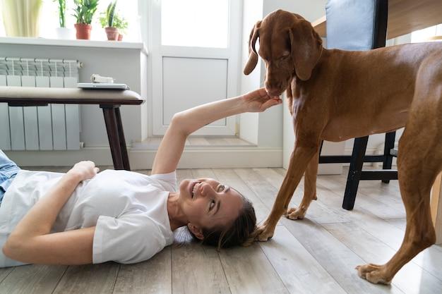 Szczęśliwa właścicielka bawi się z psem vizsla leżącym na podłodze w domu. miłośnicy zwierząt.