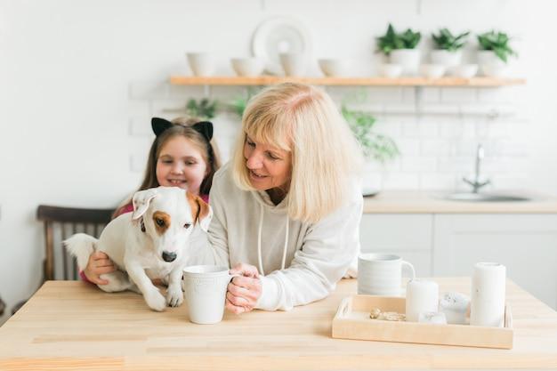 Szczęśliwa wnuczka i babcia w kuchni z psem jack russell terrierem babcią i