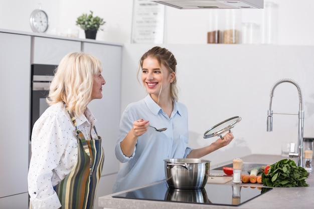 Szczęśliwa wnuczka i jej babcia gotuje zupę warzywną