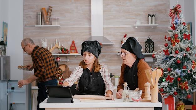 Szczęśliwa wnuczka przygotowująca ciasto piernikowe za pomocą wałka do ciasta