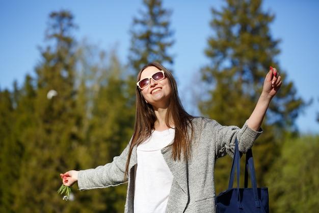 Szczęśliwa wolna kobieta w parku w okularach przeciwsłonecznych, uśmiechnięta z uniesionymi rękami.