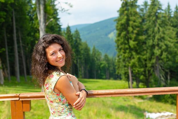 Szczęśliwa wspaniała dziewczyna cieszyć się widokiem na góry w letniej sukience na wzgórzu