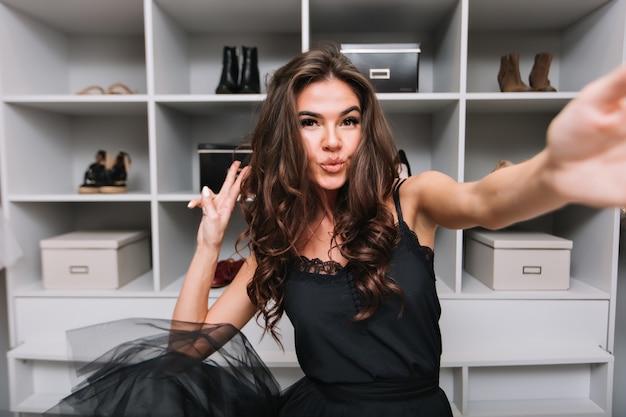 Szczęśliwa wspaniała młoda kobieta z kręconymi brązowymi włosami, taniec i robienie selfie w jej garderobie. pokazuje pocałunek. cieszy się miłym dniem. ubrana w czarną sukienkę.