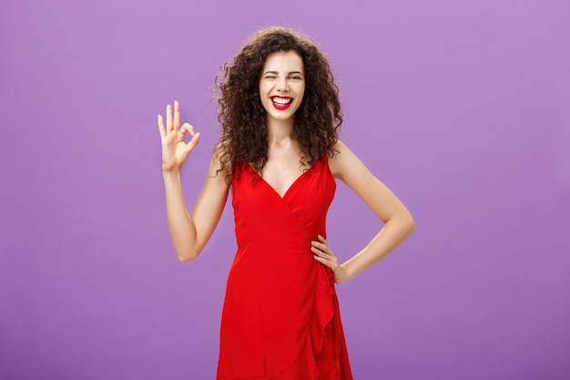 Szczęśliwa wychodząca, elegancka, elegancka europejka z kręconą fryzurą w czerwonym fasonie...