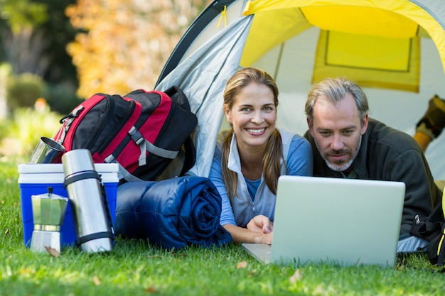 Szczęśliwa wycieczkowicz para używa laptop