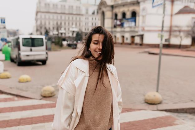Szczęśliwa wyszła kobieta o ciemnych włosach latających na sobie stylowy wiosenny strój spacery i zabawy na zewnątrz w dobry wiosenny dzień