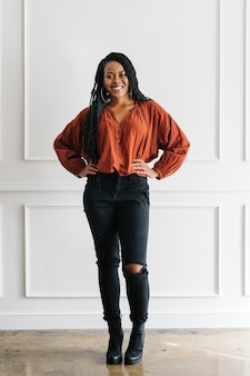 Szczęśliwa, wzmacniająca czarna kobieta stojąca przy białej ścianie