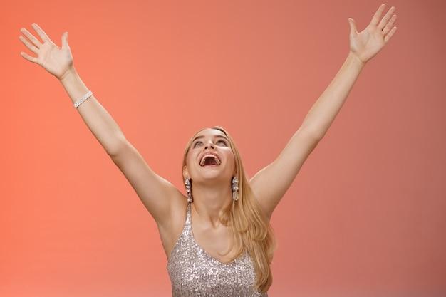 Szczęśliwa, wzruszająca uśmiechnięta przytłoczona młoda blond kobieta w srebrnej sukience podnieś ręce niebo dzięki bogu radośnie podpisana umowa dostała pracę radując się czerwonym tle świętuje zwycięstwo dobre wieści, triumf.