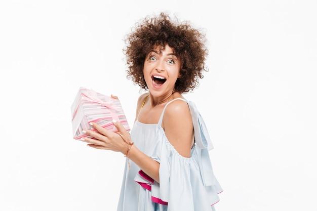 Szczęśliwa z podnieceniem kobieta trzyma teraźniejszego pudełko