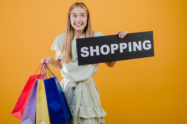 Szczęśliwa z podnieceniem ładna młoda kobieta z zakupy znakiem i kolorowymi torba na zakupy odizolowywającymi nad kolorem żółtym