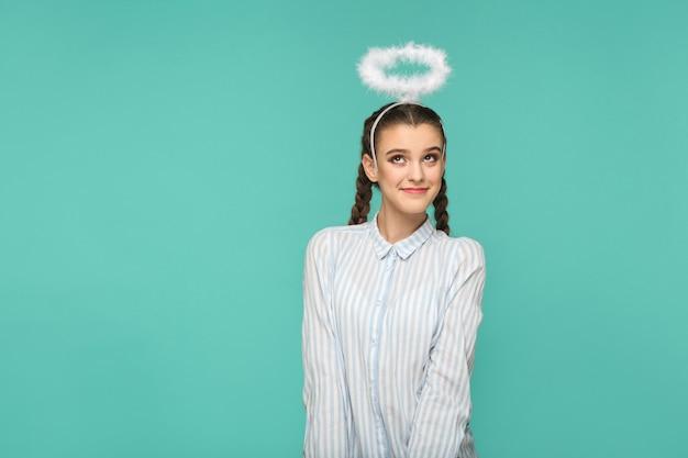 Szczęśliwa zabawna dziewczyna w pasiastą niebieską koszulę i fryzurę warkocz, stojąc z aureolą na głowie i odwracając wzrok z uśmiechem i marzącą twarzą, strzał w studio, na białym tle na niebieskim lub zielonym tle