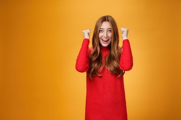 Szczęśliwa zachwycona i wesoła ruda dziewczyna z piegami i niebieskimi oczami triumfuje krzycząc tak z szerokim uśmiechem zaciskając wzniesione pięści z radości i świętując sukces na pomarańczowym tle
