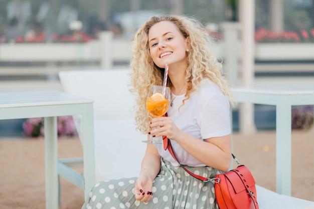 Szczęśliwa zachwycona kręcona młoda kobieta ubrana w białą koszulkę i długą spódnicę, trzyma kieliszek koktajlu, cieszy się słoneczny dzień i dobre wakacje, ma manicure, uśmiecha się radośnie. koncepcja ludzie i wakacje