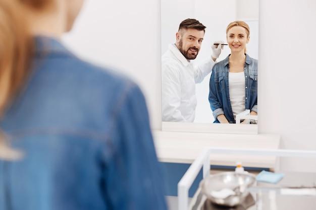 Szczęśliwa zachwycona pozytywna kobieta patrząc na swoje odbicie i uśmiechnięta podczas wizyty u chirurga plastycznego