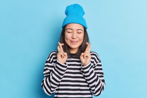 Szczęśliwa zadowolona azjatycka nastolatka krzyżuje palce i oczekuje rezultatów, trzyma oczy zamknięte, wierzy, że marzenia się spełniają, nosi swobodny sweter w paski i kapelusz