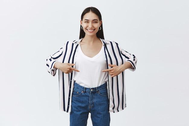 Szczęśliwa zadowolona kobieta stojąca w modnym stroju i wskazująca na brzuch, pokazująca, że schudła, chwaląca się wynikami po wizycie na siłowni, stojąca zdrowo i wysportowana na szarej ścianie