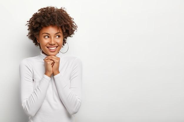 Szczęśliwa zadowolona kobieta trzyma ręce razem pod brodą, patrzy na bok z radością