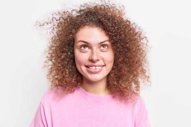 Szczęśliwa zadowolona kobieta z naturalnymi kręconymi włosami skupiona nad dostrzega coś śmiesznego na suficie, uśmiecha się ubrana w codzienną koszulkę na białym tle nad białą ścianą. koncepcja pozytywnych emocji