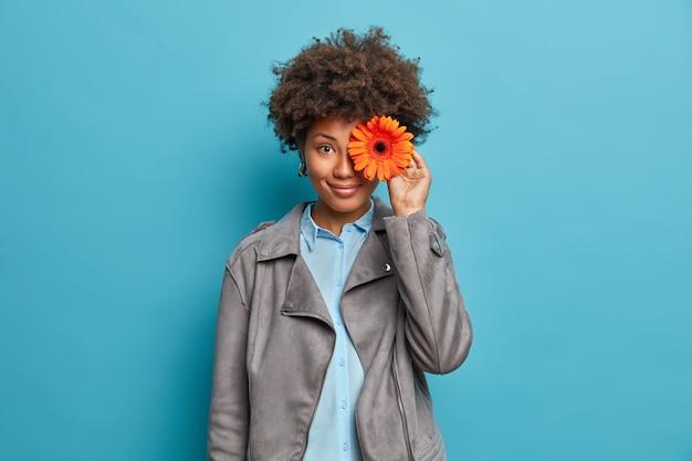Szczęśliwa, zadowolona młoda afroamerykanka kwiaciarka składa bukiet z gerbera, pracuje w kwiaciarni, nosi szarą kurtkę, ma przyjemny uśmiech,