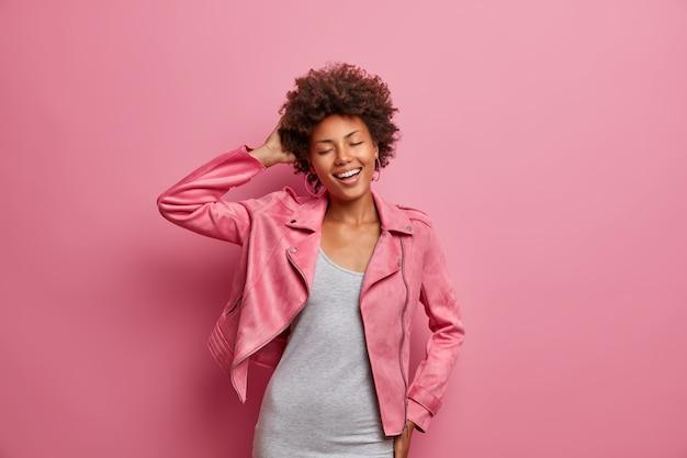 Szczęśliwa zadowolona młoda kobieta zamyka oczy, czuje przyjemność słuchając ulubionej muzyki, bawi się przy tańcach