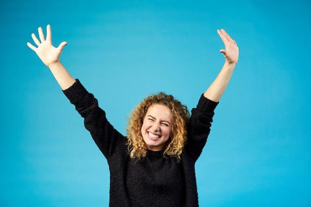Szczęśliwa zadowolona młoda rudzielec kędzierzawa kobieta świętuje sukces i rozwesela sukces z radością rozprzestrzenia ręki przeciw błękitowi