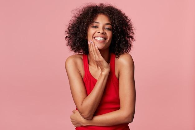 Szczęśliwa zadowolona urocza afroamerykańska dziewczyna z fryzurą afro wygląda z przyjemnością, dotyka jej twarzy dłonią, uśmiecha się, raduje się z miękkiej skóry, nosi czerwony podkoszulek, odizolowany