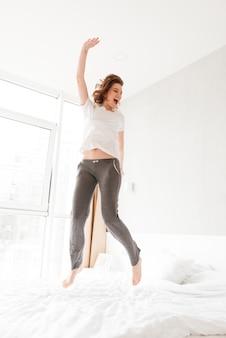 Szczęśliwa zadziwiająca młoda kobieta w łóżku indoors skacze