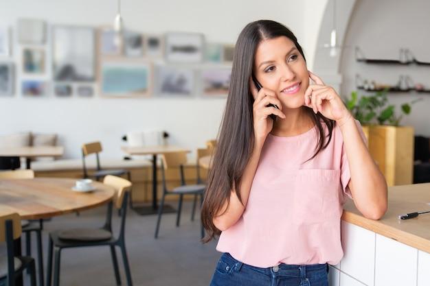 Szczęśliwa zamyślona młoda kobieta rozmawia przez telefon komórkowy, stojąc przy co-working, opierając się na biurku, odwracając wzrok i uśmiechając się