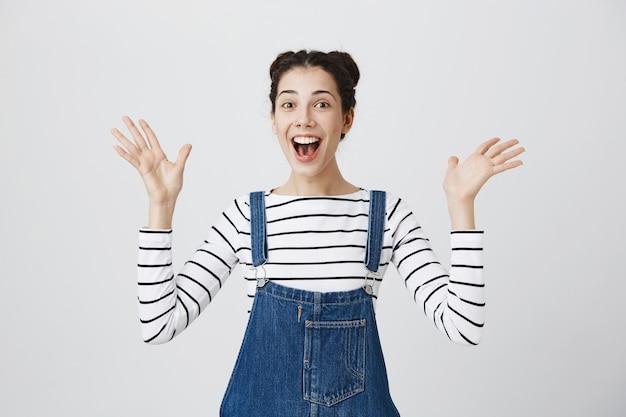 Szczęśliwa zaskoczona dziewczyna podnosząca ręce do góry i uśmiechnięta rozbawiona, opisująca wspaniałe wieści