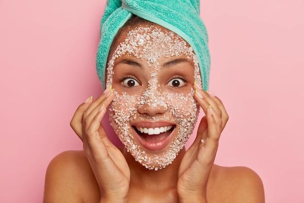 Szczęśliwa zaskoczona kobieta chce odświeżyć twarz, złuszcza się naturalną maską z soli morskiej, uśmiecha się grymasem do aparatu, szeroko otwarte ciemne oczy owinięte ręcznikiem na głowie, stoi w pomieszczeniu