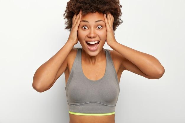Szczęśliwa zaskoczona kobieta trzyma obie ręce na głowie, reaguje na niesamowite trafienie, ma otwarte usta, ubrana w szary stanik