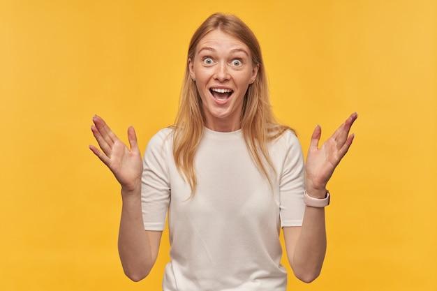 Szczęśliwa zaskoczona kobieta z piegami w białej koszulce trzyma ręce uniesione i wygląda na zdziwioną na żółto