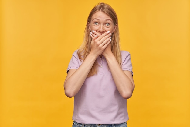 Szczęśliwa zaskoczona kobieta z piegami w lawendowej koszulce wygląda na zdziwioną i stożkowatą ustami rękami na żółto
