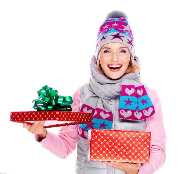 Szczęśliwa zaskoczona kobieta z prezentem świątecznym w zimowej odzieży wierzchniej na białym