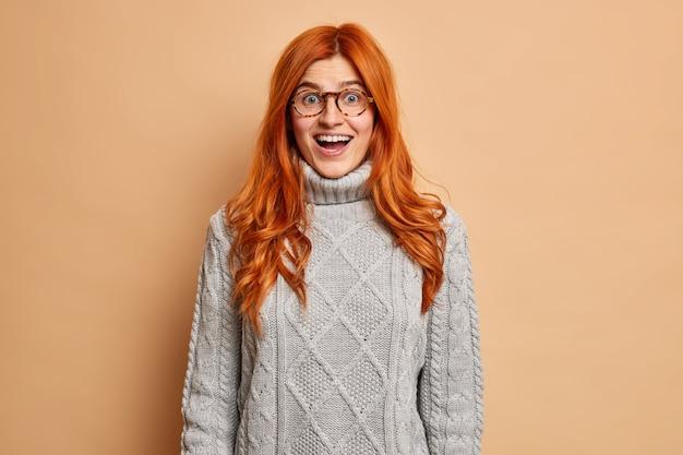 Szczęśliwa zaskoczona ruda kobieta wygląda z otwartymi ustami, nie może uwierzyć w jej nagły sukces ubrany w sweter z dzianiny.