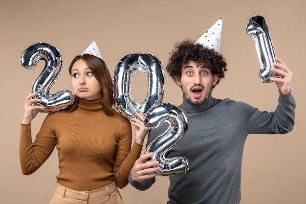 Szczęśliwa zdezorientowana niepewna młoda para nosi kapelusz noworoczny pozuje do kamery dziewczyna pokazuje i facet z i na szaro