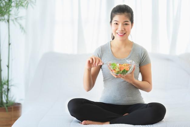 Szczęśliwa zdrowa azjatycka kobieta je jarzynowej sałatki dla diety