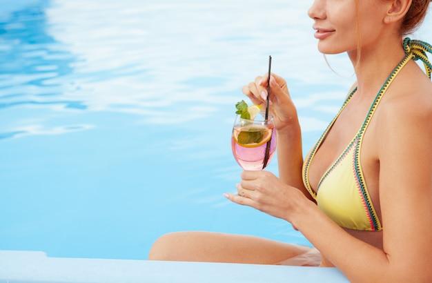 Szczęśliwa zdrowa kobieta relaksuje przy hotelowym poolside