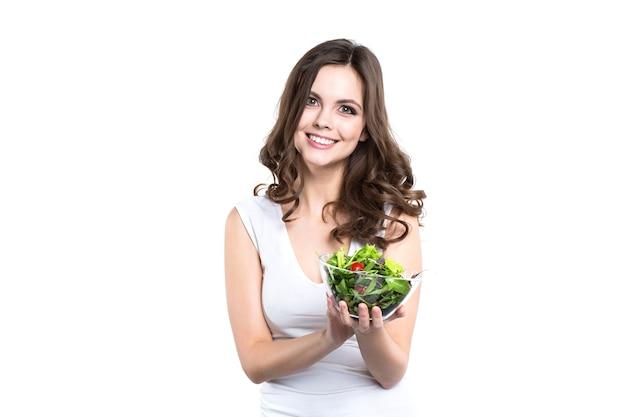 Szczęśliwa zdrowa kobieta z sałatką na białym tle. zdrowy tryb życia.