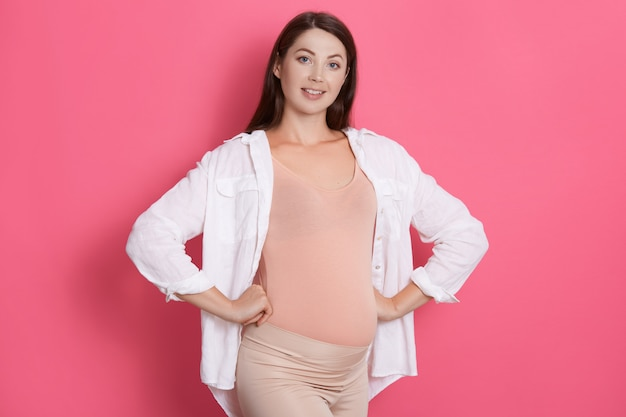 Szczęśliwa zdrowa młoda kobieta w ciąży stojąc z rękami na biodrach