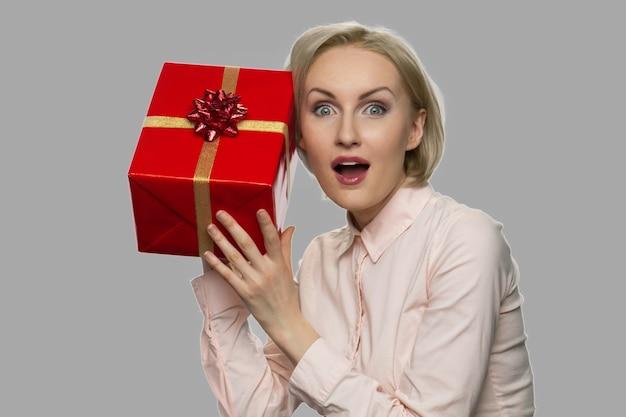 Szczęśliwa zdumiona kobieta trzyma pudełko. zaskoczona radosna kobieta trzyma zapakowane pudełko. nieoczekiwany prezent. koncepcja premii wakacyjnej.