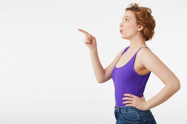 Szczęśliwa zdumiona młoda atrakcyjna krótkowłosa dziewczyna, ubrana w fioletową koszulkę, zobaczyła coś niezwykle interesującego i wskazuje palcem, spójrz na przestrzeń kopii odizolowaną na białej ścianie.