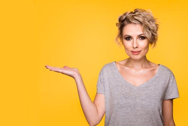 Szczęśliwa zdziwiona blondynka młoda kobieta uśmiecha się szeroko do kamery, wskazując palcami, pokazując coś ciekawego i ekscytującego na żółtym tle studio z miejscem na kopię tekstu