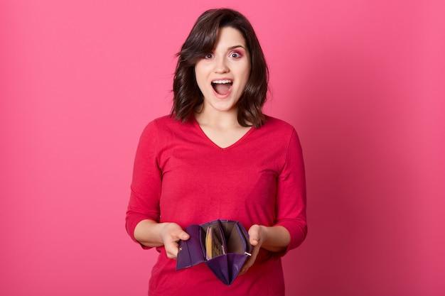 Szczęśliwa zdziwiona kobieta trzyma portfel pełen pieniędzy, wygrywa dużą sumę pieniędzy, stoi z szeroko otwartymi ustami i podekscytowanym wyrazem twarzy, dama w czerwonej koszuli.