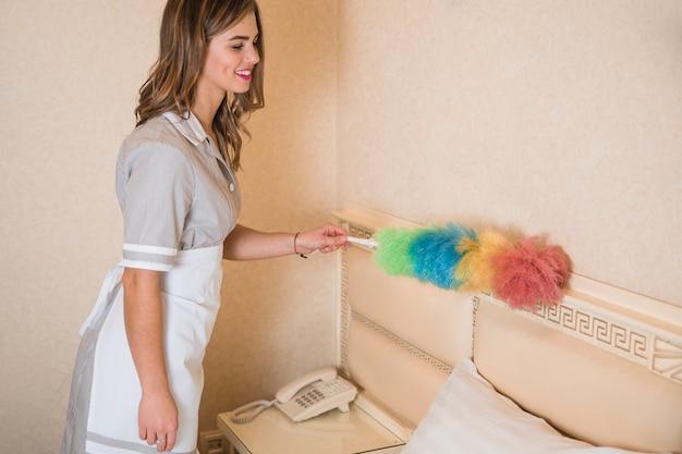 Szczęśliwa żeńska gosposia używa duster czyścić ścianę pokój hotelowy