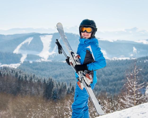 Szczęśliwa żeńska narciarka ono uśmiecha się kamera, trzyma jej narty, przy zima ośrodkiem narciarskim