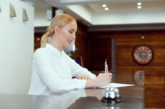 Szczęśliwa żeńska recepcjonistka stoi przy hotelowym kontuarze