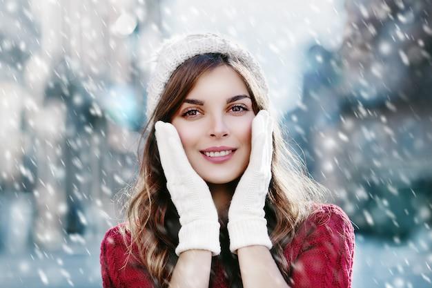 Szczęśliwa zimy śnieżna dziewczyna w kapeluszu i rękawiczkach bożenarodzeniowego nowego roku