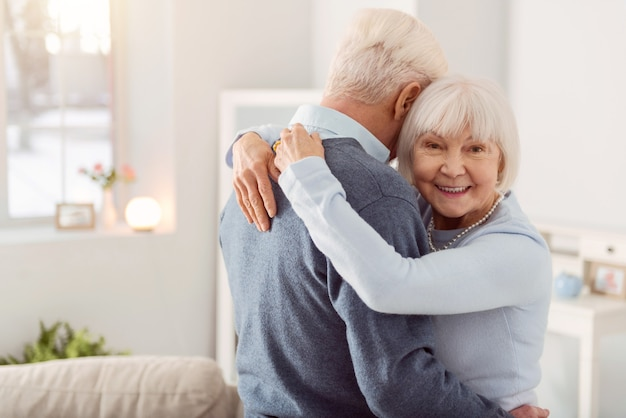 Szczęśliwa żona. przyjemna starsza kobieta uśmiecha się przytulając swojego ukochanego męża podczas tańca
