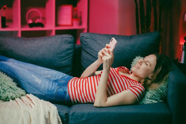 Szczęśliwa zrelaksowana kobieta trzyma mądrze telefon używać mobilne aplikacje ogląda śmiesznego wideo śmia się kłamać na leżance